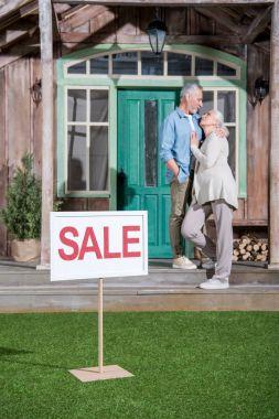 Senior couple near house for sale