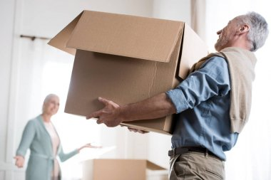 Side view of man holding heavy cardboard box at new home stock vector