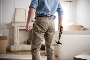 man with hammer standing in room