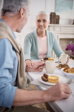 elderly couple having breakfast at home