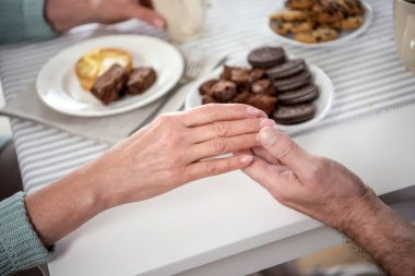 couple holding hands during breakfast