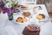 Photo lilac flowers with tea and various pastry