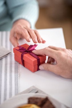 Cropped shot of man presenting gift in box with ribbon to his wife stock vector