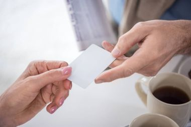 man passing blank card to woman