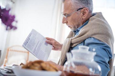 man reading newspaper during breakfast