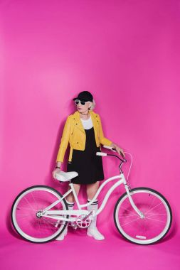 Stylish senior woman wearing black dress and yellow leather jacket standing with bicycle isolated on pink stock vector