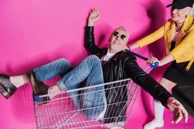 Smiling stylish senior woman pushing shopping trolley with joyful senior man having fun stock vector