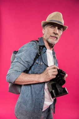Portrait of confident man in hat holding photo camera and looking away isolated on pink stock vector