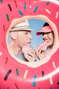 elderly couple eating sweet doughnuts
