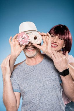 elderly couple fooling around with doughnuts