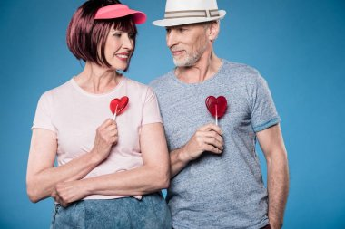 fashionable elderly couple holding lollipops
