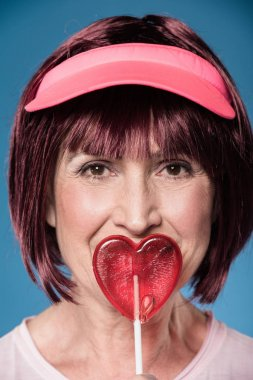 woman licking lollipop in form of heart