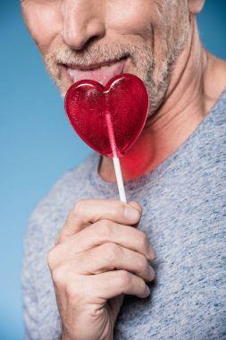 man licking lollipop in form of heart