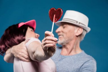 elderly couple hugging and holding lollipop