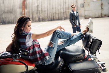 Beautiful young woman in denim vest sitting on motorcycle and stylish man in sunglasses standing behind stock vector