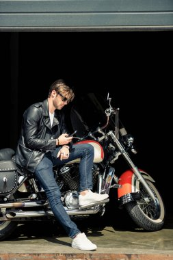Handsome young man in sunglasses and leather jacket sitting on motorcycle and using smartphone stock vector