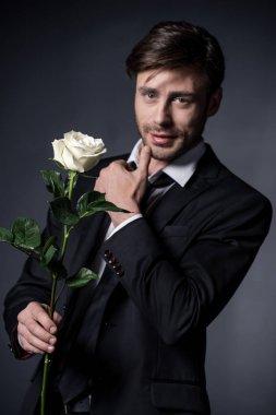 man holding rose and looking at camera