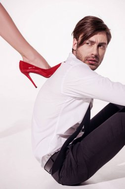 Woman stepping on man with red stiletto