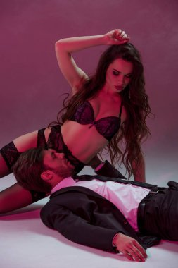 man lying and touching girl in lingerie