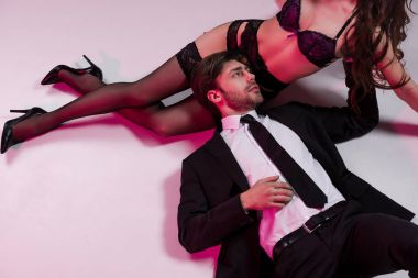 man lying and touching woman in lingerie