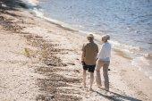 starší pár kráčející na pláži
