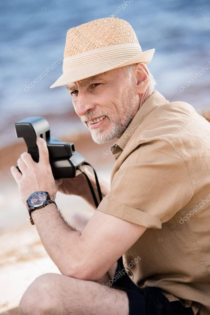 Senior man with instant camera