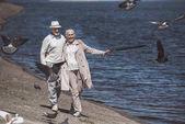 Fotografia Coppie anziane che camminano sulla riva del fiume