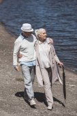 Seniorenpaar geht am Ufer des Flusses spazieren