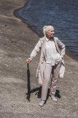 Starší žena pózuje s deštníkem na riverside