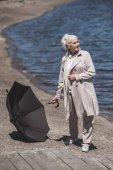 Seniorin posiert mit Regenschirm am Flussufer