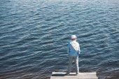 Fotografie legerer Mann stehend auf Kai tagsüber