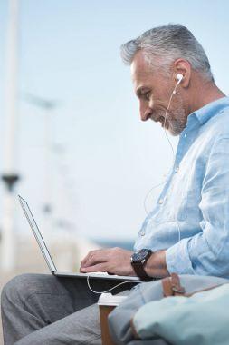 senior man working on laptop outdoors