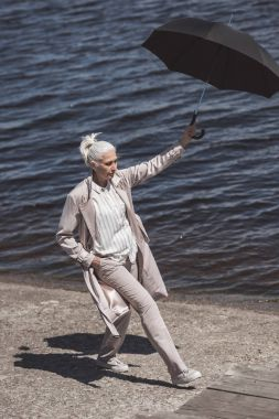 woman walking with umbrella on river shore