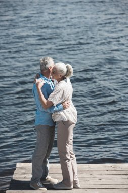 grey haired couple hugging on riverside
