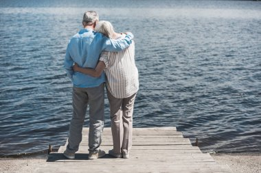 senior couple embracing while standing on riverside