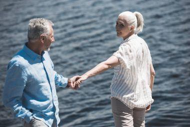 Elderly couple holding hands on riverside