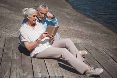 elderly couple reading book on quay