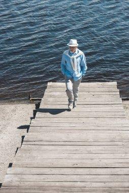 stylish senior man walking on riverside