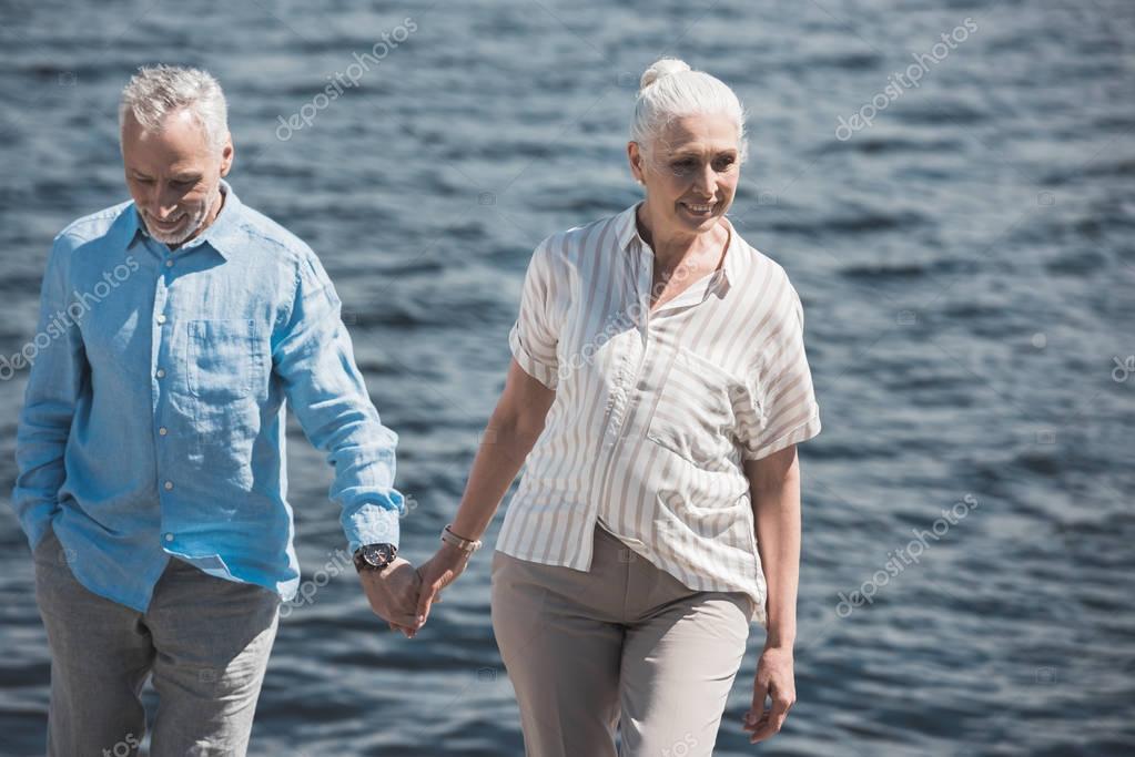 smiling elderly couple walking on riverside