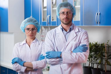Scientists in lab coats standing with arms crossed at chemical laboratory during work stock vector