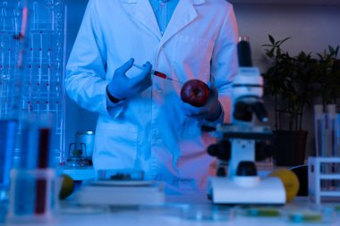 Scientist with syringe and apple