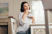 mladá žena pití kávy v domácnosti