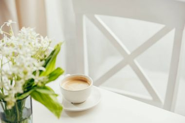 cup of coffee with bouquet of flowers on tabletop