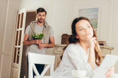 man with bouquet of flowers looking at girlfriend