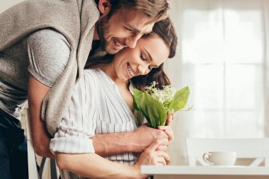 couple hugging and holding flowers at home