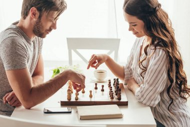 Young couple playing chess while sitting at table at home stock vector