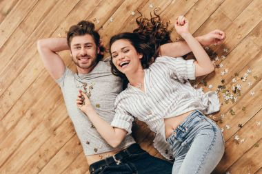 young smiling couple lying on floor