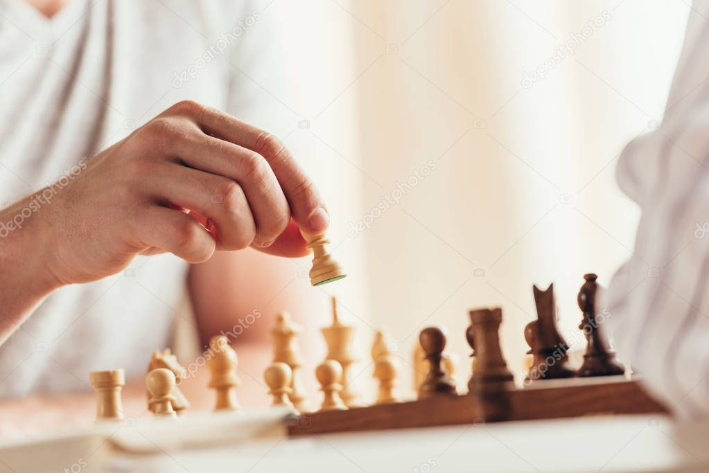 man moving chess figure during game