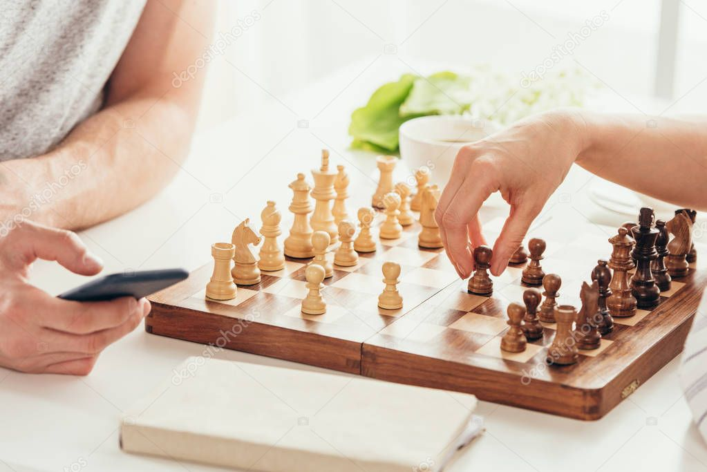 young couple playing chess at home