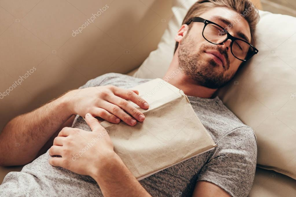 young man sleeping with book at home